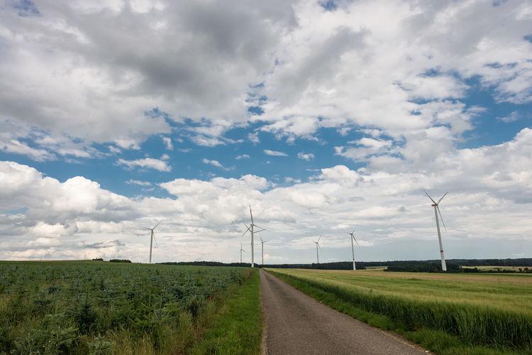Street amidst wind turbines against cloudy sky