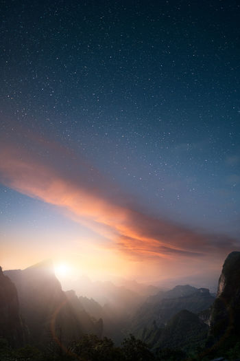 Epic artistic vertical landscape view from Tianmen mountain in Zhangjiajie with beautiful sunset and a star sky. Scenics - Nature Sky Beauty In Nature Mountain Star - Space Night Tranquility Tranquil Scene Space Astronomy Nature Environment Mountain Range Idyllic Non-urban Scene Landscape No People Galaxy Star Star Field Outdoors Vertical Book Cover Magazine Cover Copy Space