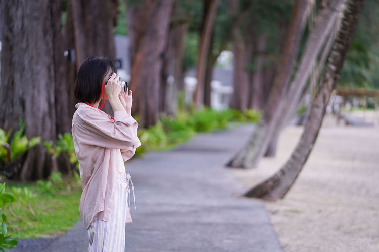Side view of woman standing on mobile phone outdoors