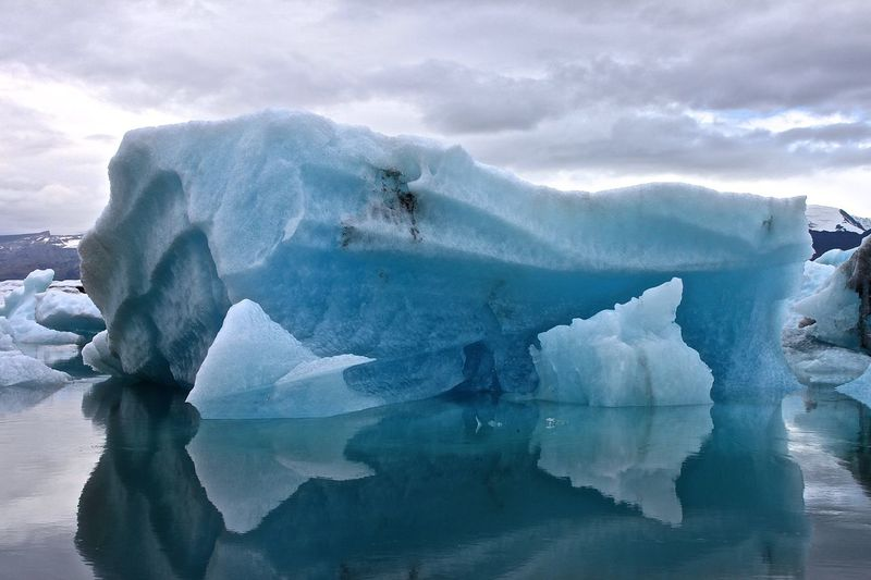 Reflection Of Iceberg In Jokulsarlon Lake Against Cloudy Sky