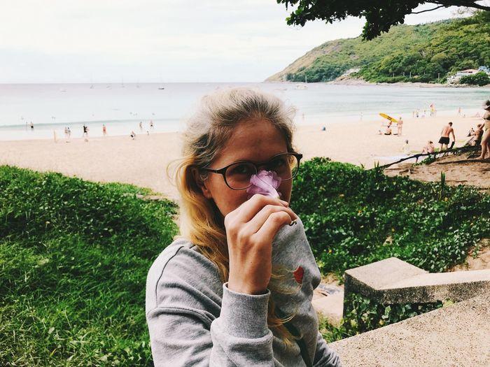 Portrait of woman smelling flower against sea