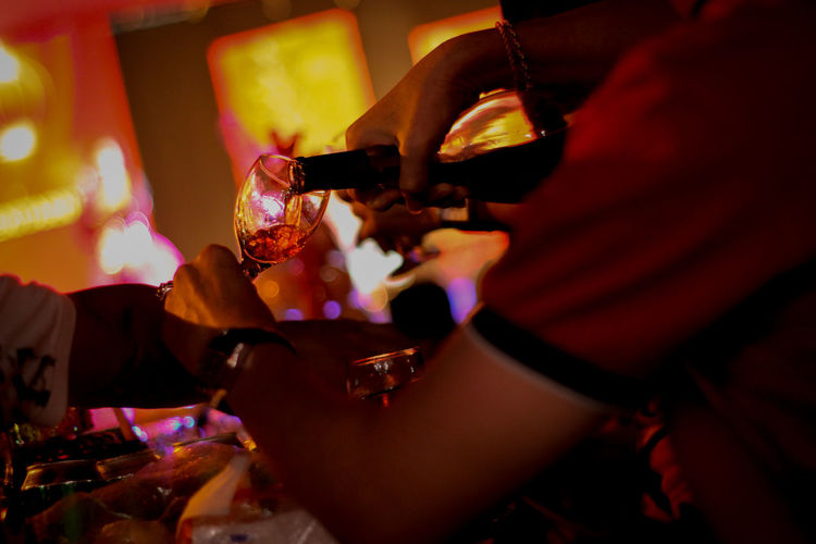 Midsection of man pouring wine from bottle in glass at restaurant