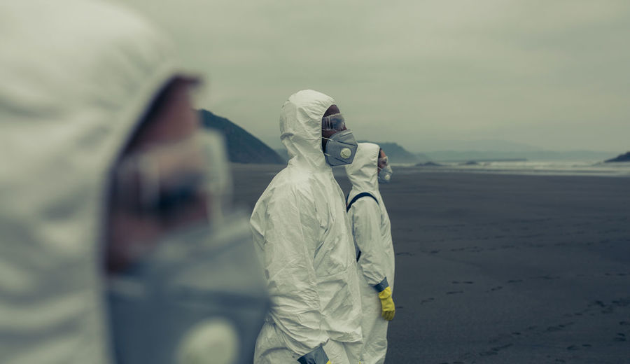 Doctors in protective workwear standing at beach