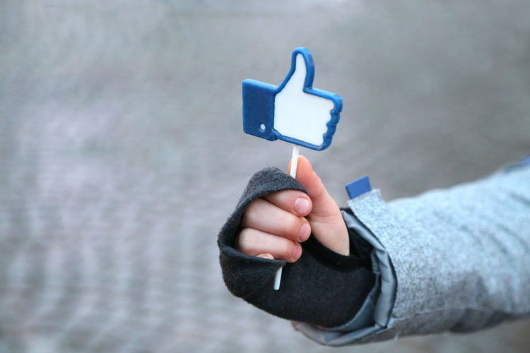 Cropped hand of child holding thumbs up icon