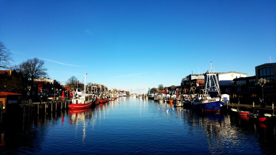 Boats moored on river against clear blue sky