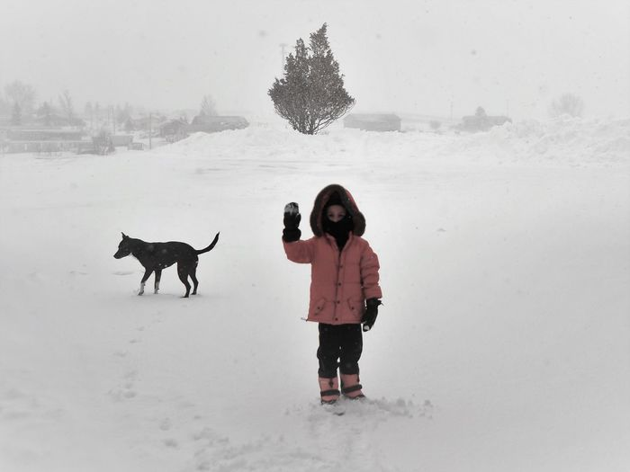 Boy Wearing Warm Clothing Playing In Snow Against Sky During Winter