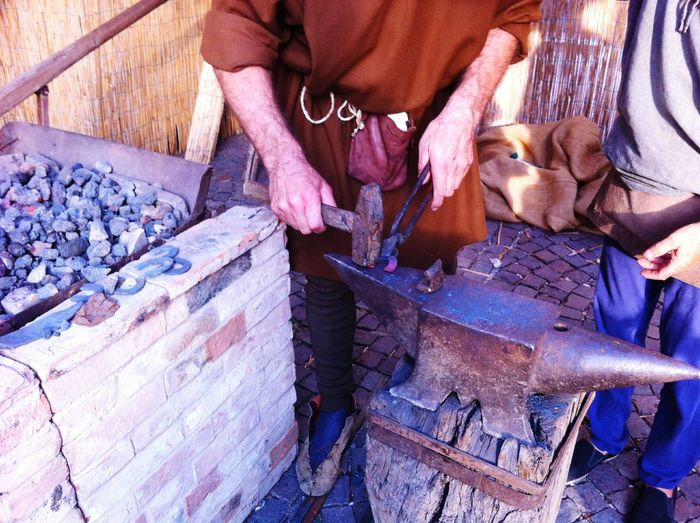 Low section of blacksmith hammering horseshoe on anvil