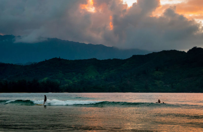 Sunset in Hanalei Bay, Kauai, Hawaii. Adult Beach Beauty In Nature Cloud - Sky Day Full Length Leisure Activity Lifestyles Men Mountain Nature One Man Only One Person Only Men Outdoors People Real People Scenics Sea Sky Standing Tree Water