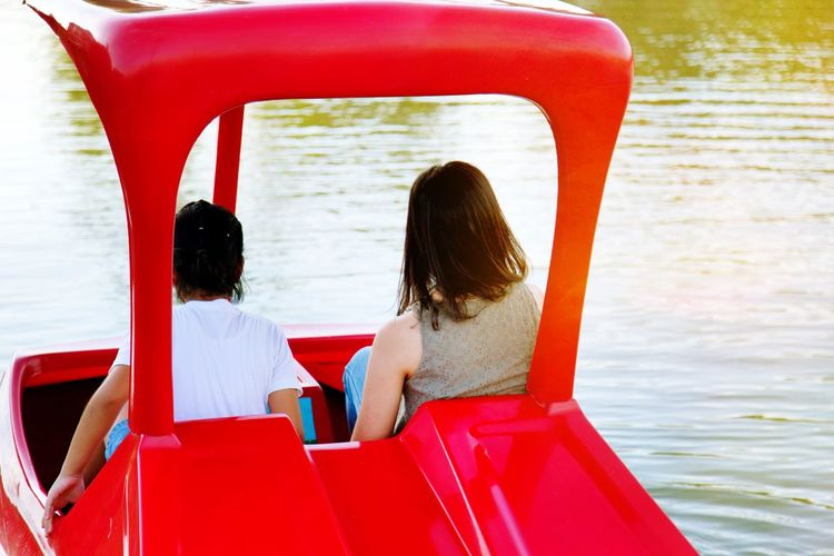 Rear view of girl and woman sitting in pedal boat on lake