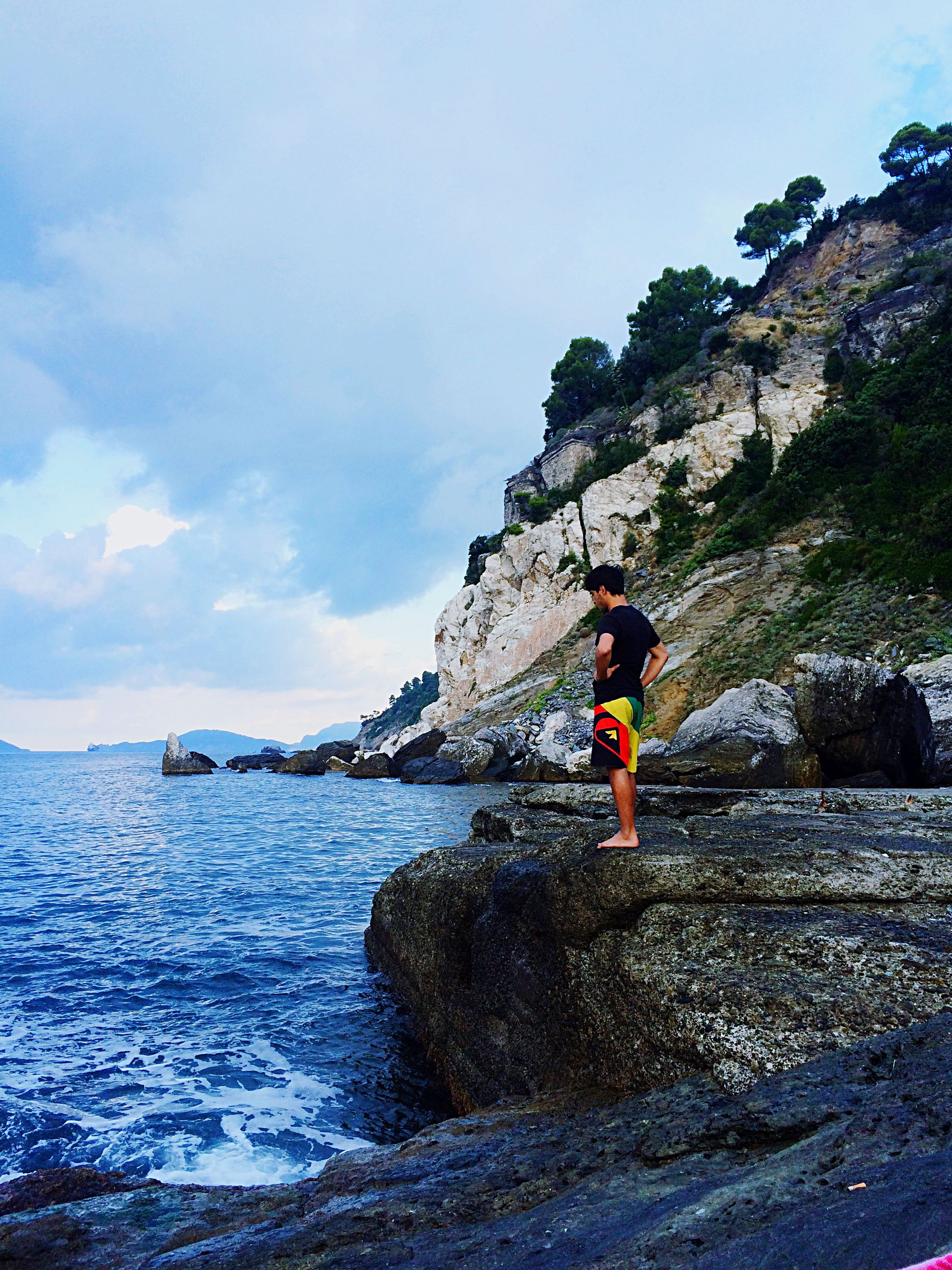 water, sea, lifestyles, sky, leisure activity, full length, standing, men, rear view, rock - object, beach, scenics, tranquil scene, nature, shore, tranquility, person, beauty in nature