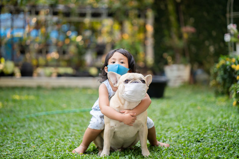 Little girl and her french bulldog wearing medical mask prevent pollution, flu and convid19 at park.