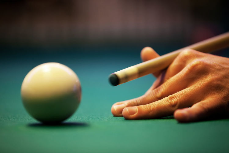 Cropped Hand Of Man Playing Pool