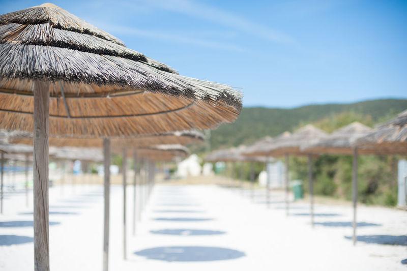 Sunshades At Beach Resort Against Sky On Sunny Day
