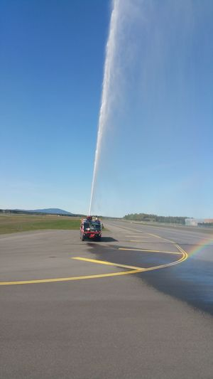 Fire engine splashing water on road against blue sky