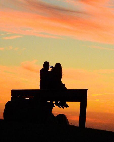 Silhouette couple sitting against orange sky