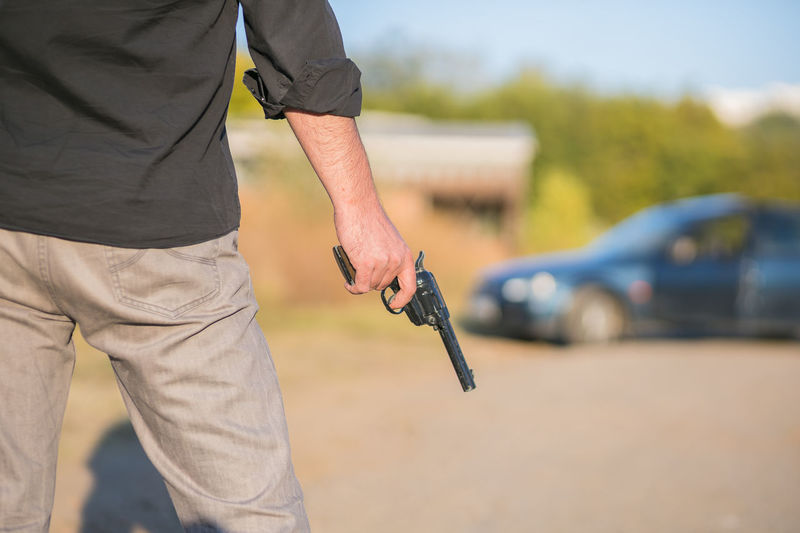 Midsection of man holding gun outdoors