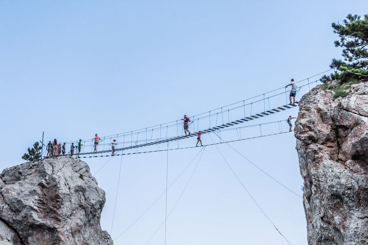 Low angle view of people walking on footbridge against clear sky