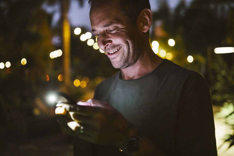 Portrait of young man using mobile phone at night
