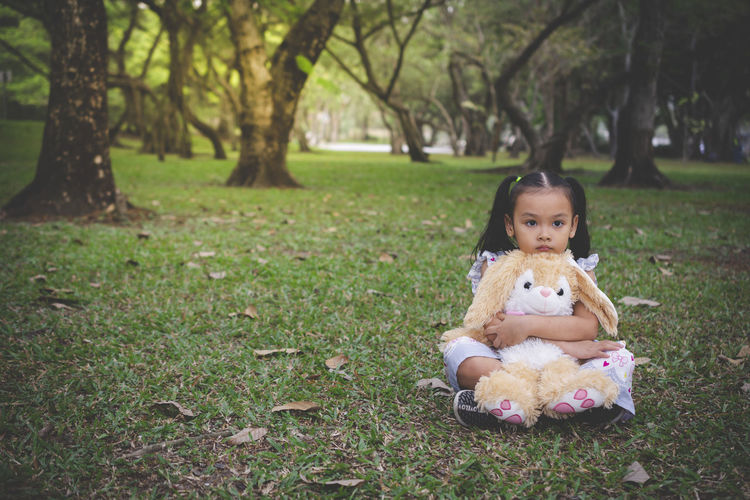 Portrait of innocent girl sitting with stuffed toy at park