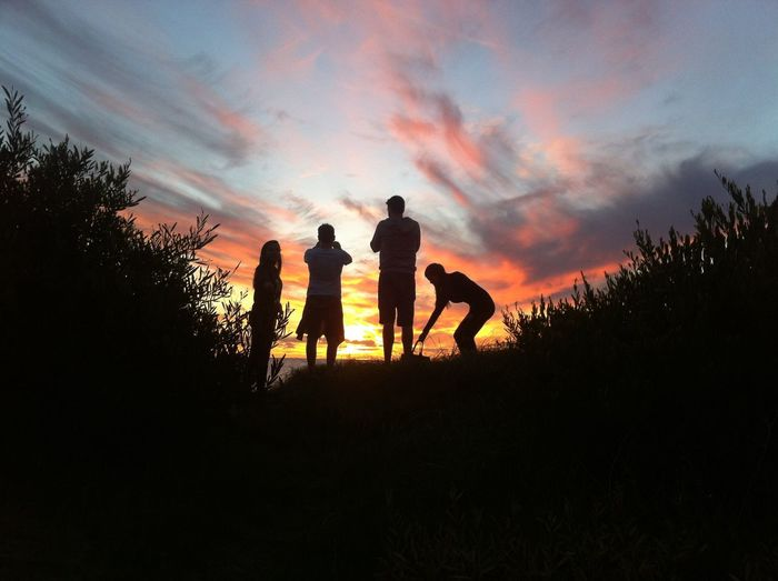 Silhouette of friends against cloudy sky