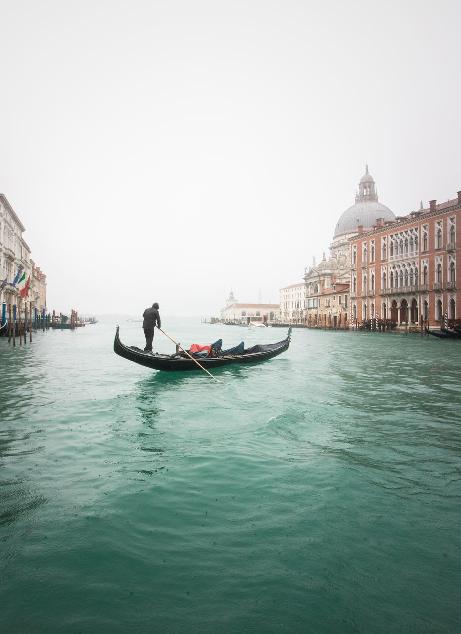 nautical vessel, one person, water, mode of transportation, transportation, real people, gondola - traditional boat, waterfront, canal, sky, architecture, building exterior, travel, built structure, nature, gondolier, day, men, outdoors