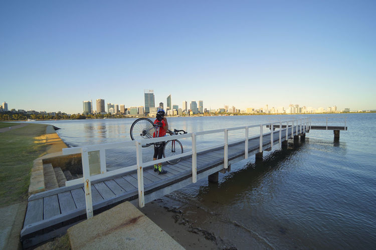 PERTH, AUSTRALIA - DECEMBER 20, 2016: tourist looking at the city in the sunset Bicycle City Clear Sky Day Men Nature One Person Outdoors People PERTH, AUSTRALIA - DECEMBER 20, 2016: Tourist Looking At The City In The Sunset Sky Urban Skyline Water