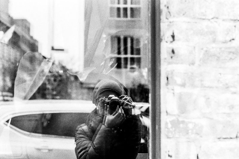 Woman photographing while standing in front of window display