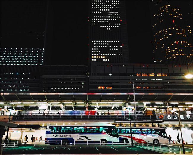 Buses outside illuminated nagoya station in city at night