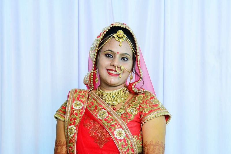 Portrait of smiling bride wearing jewelries and traditional clothing standing against curtain