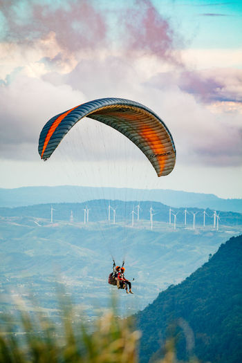 Person paragliding flying against sky