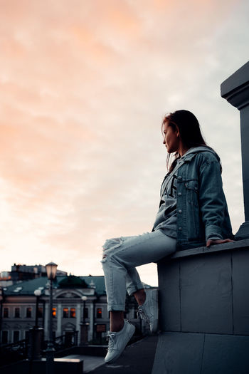 Low angle view of woman looking at city against sky