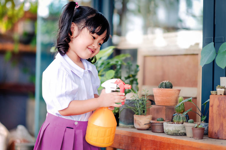 Smiling Cute Girl Spraying Water On Potted Plant