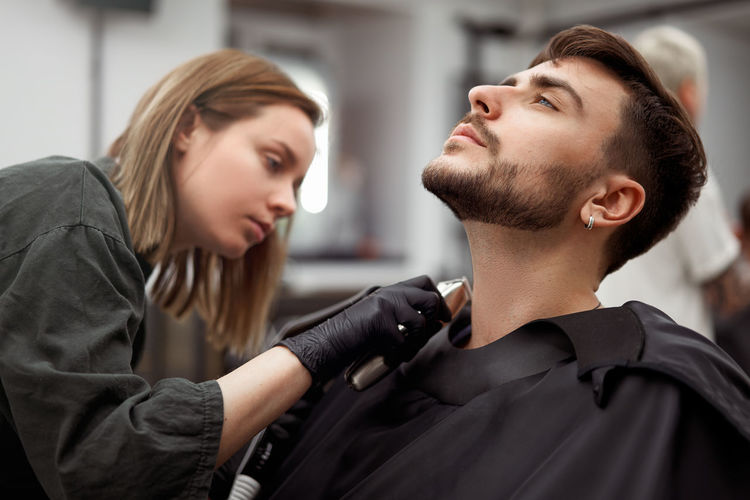 Portrait of young man who sitting in barbershop and woman hairdresser cut hair