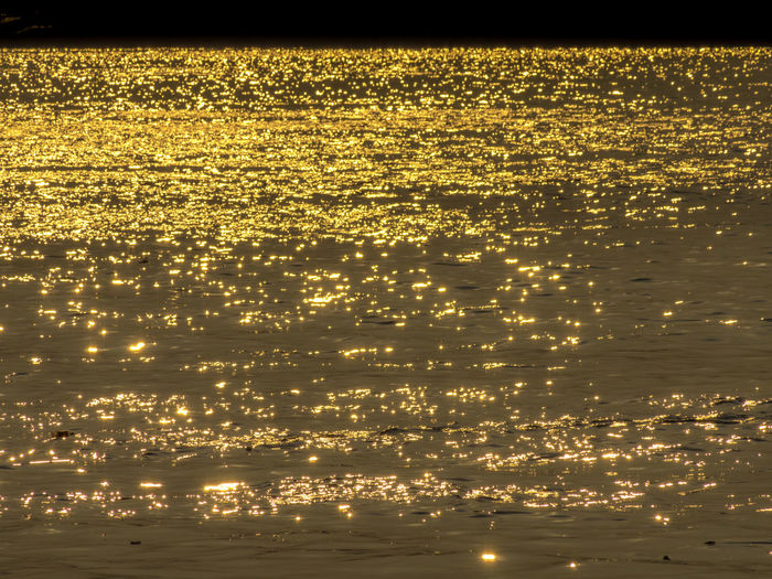 Abstract emotion blur of sun light shining on water surface. Bokeh of water surface level in low light. Yellow and orange light from the sun make reflection with water. Dazzling Reflex Wave Beach Beauty In Nature Blurred Motion Bokeh Gold Colored Illuminated Nature No People Orange Color Outdoors Reflection River Scenics - Nature Sea Shiny Sunlight Sunset Surface Level Tranquil Scene Tranquility Water Waterfront