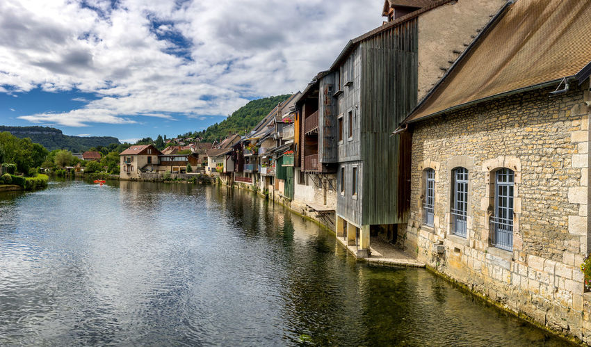 Typical houses on riverbanks in Ornans, France France Ornans Architecture Building Exterior Built Structure Cloud - Sky Day House Mountain Nature Nautical Vessel No People Outdoors Reflection Residential Building River Scenics Sky Tranquility Travel Destinations Water Waterfront Window