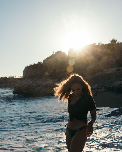 Young woman standing at beach against bright sun in clear sky