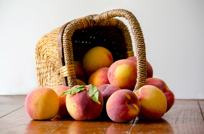 Tipped basket of fresh picked peaches Agriculture Basketball Fall Colors Freshness Nature USA Basket Container Food Food And Drink Freshness Fruit Healthy Eating Indoors  Juicy Fruit Michigan Peaches Orange Color Organic Peanuts Peach Spilling Out Still Life Table Wellbeing Wood - Material Yellow