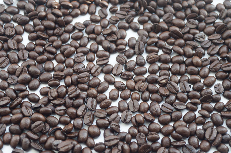 Full frame shot of roasted coffee beans on white background
