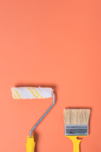 Close-up of paintbrushes against orange wall