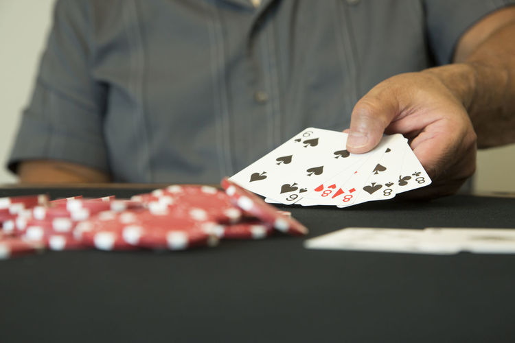 Casino chips and playing cards on a poker table. Arts Culture And Entertainment Cards Finger Gambling Game Of Chance Hand Holding Human Body Part Human Hand Indoors  Leisure Activity Leisure Games Luck Men Midsection One Person Opportunity Playing Poker - Card Game Real People Relaxation Table