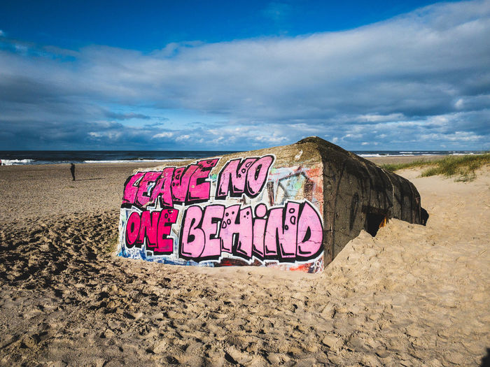 Text written on sand at beach against sky