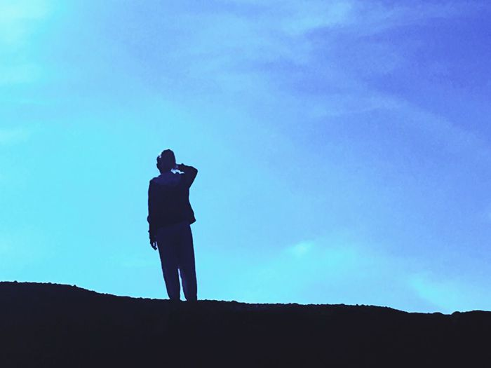 Silhouette of woman standing against blue sky