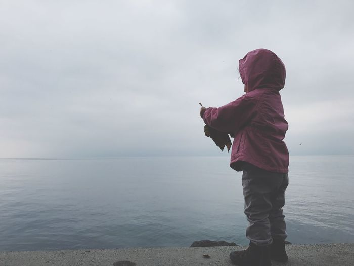 Full length of child standing by lake against cloudy sky during sunset