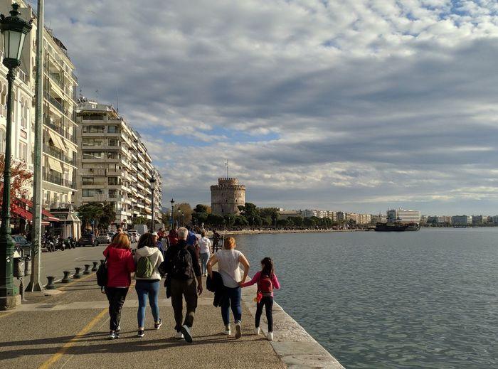 People on sidewalk by buildings in city against sky