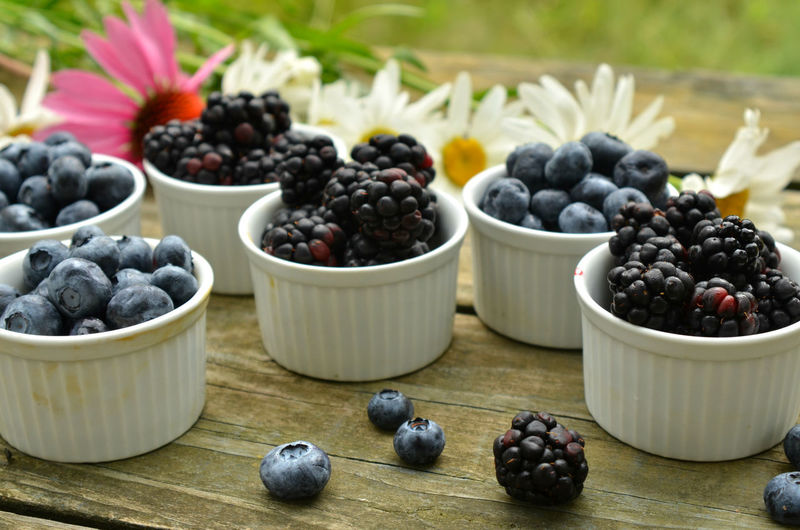 Blueberries and blackberries in small white ramekins with garden daisies on rustic wood table