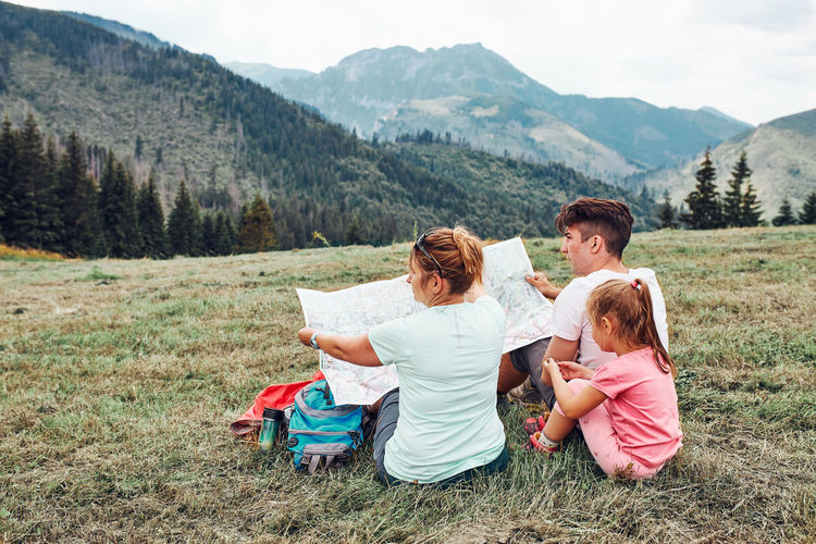 Family examining a map of mountains trials sitting on grass enjoying summer day during vacation trip