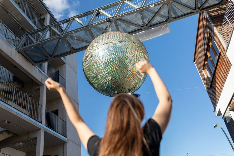 Low angle view of woman with arms raised against disco ball hanging from built structure