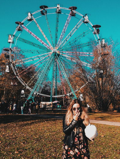 Woman holding cotton candy while standing against ferris wheel