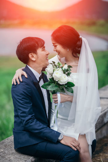 Midsection of couple holding flower bouquet