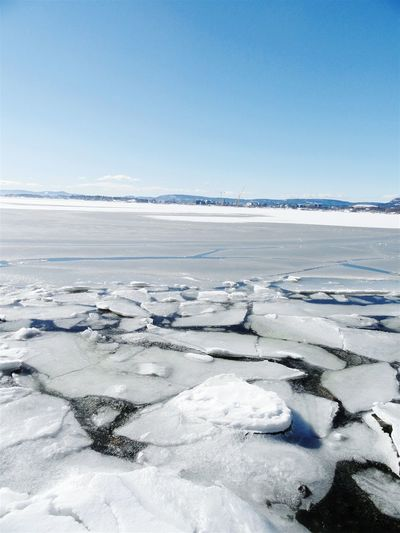 Scenic view of frozen river against clear sky